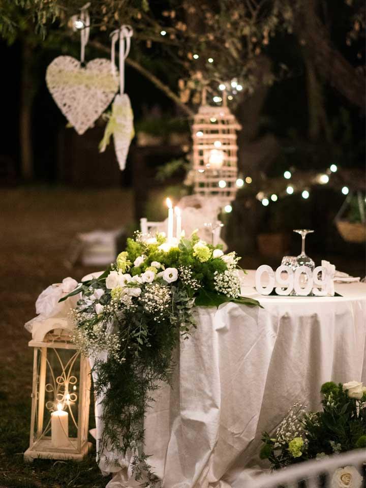 Allestimento tavolo sposi con centrotavola di rose bianche.
