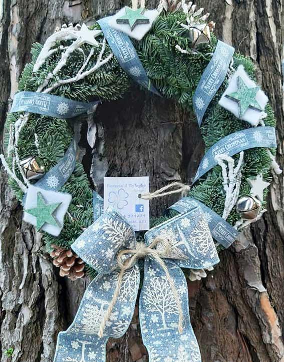 Ghirlanda di abete normandiano fresco argentato abbellita con fiocchi e pendagli di Natale