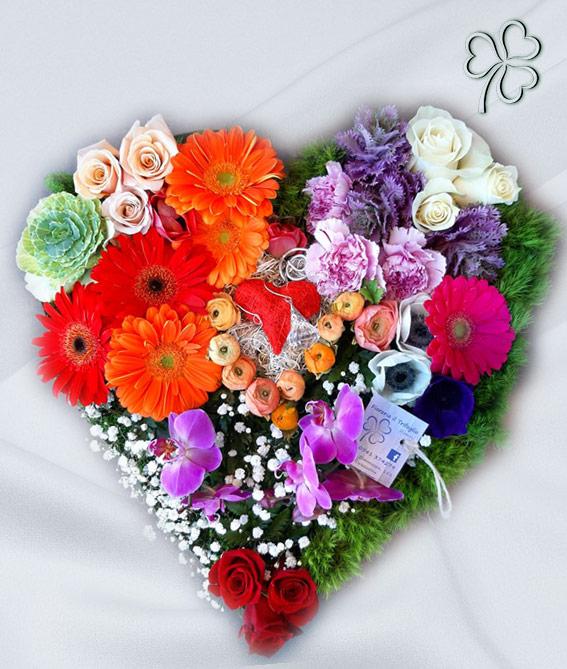 Composizione a forma di cuore con fiori misti, effetto primavera.