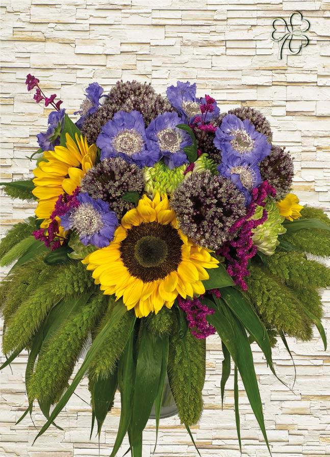Bouquet estivo con fiori di girasoli, scabiosa, fiori di allium, limonium, crisantemo, rifinito con setaria