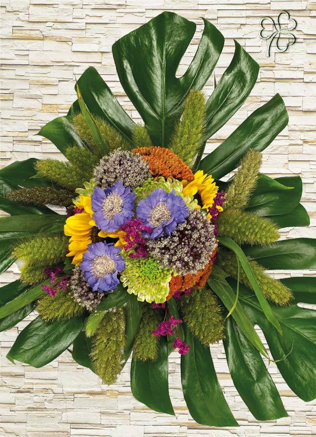 Bouquet estivo con fiori di girasole, scabiosa, fiori di allium, limonium, crisantemo, rifinito con foglie di monstera
