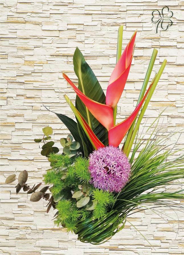 Composizione di heliconia e fiore di allium, rifinite con asparagus, bear grass, foglie di strelitzia ed eucalipto