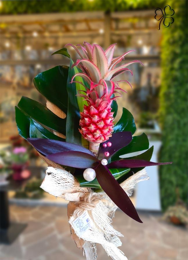 Composizione tropicale con ananas ornamentale fucsia, rifinita con foglie di monstera, tradenscantia, perle e fibre di cocco