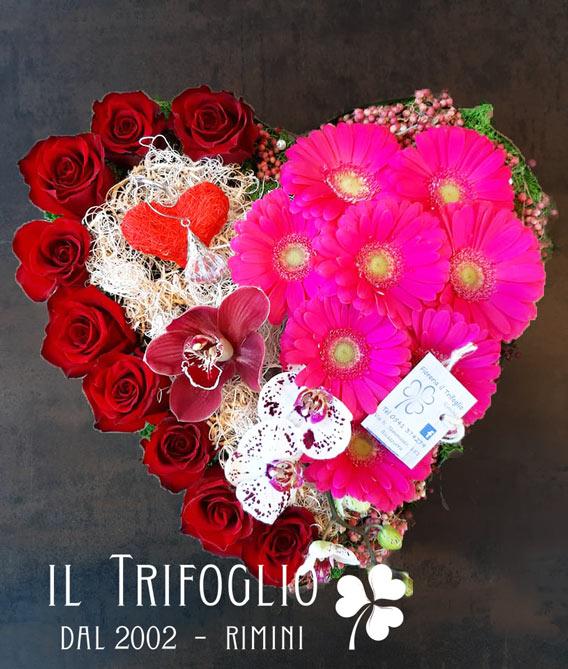 Composizione San Valentino a forma di cuore con rose rosse, orchidee variegate e gerbere fucsia.