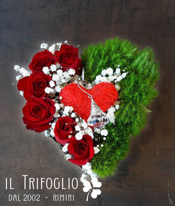 Composizione a forma di cuore realizzata con fiori freschi e abbellita con pendaglio in vetro trasparente.