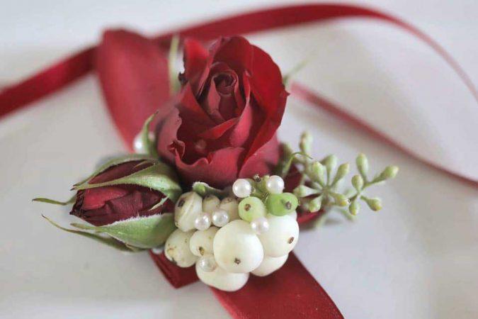 Bracciale damigella con rose rosse e bacche di pernettya bianche