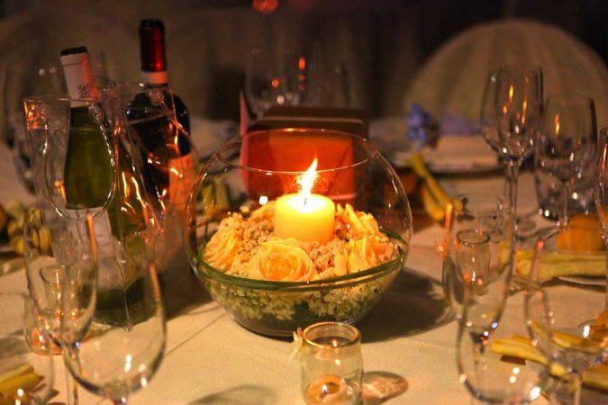 Centrotavola in boule di vetro con rose bianche, gypsophila, bear grass e candela