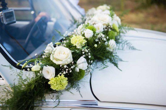 Allestimento auto degli sposi con torcione di rose bianche, lisianthus, garofano verde mela, fiore del poeta e gypsophila