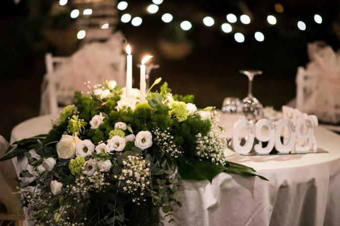 Composizione tavolo sposi scendente con candele, lisianthus bianco, garofano verde mela, gypsophila, asparagus e eucalipto